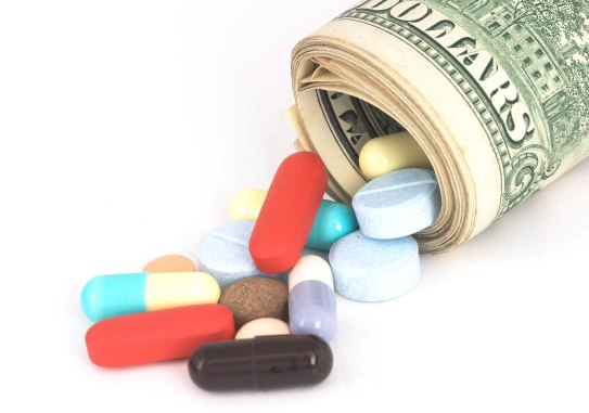 Closeup Money rolled up with pills falling out, high cost, expensive healthcare